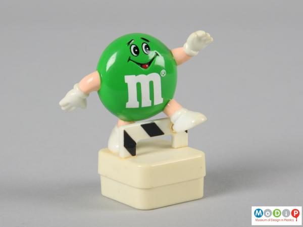 Front view of a green M&M figure showing the smiling face and the limbs.