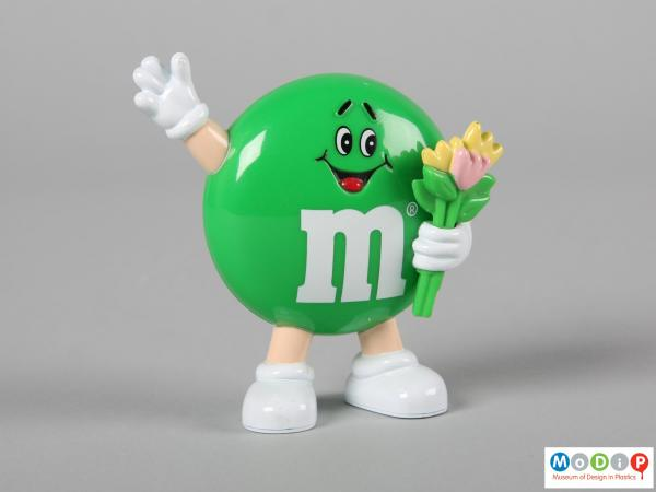Front view of a green M&M figure showing the smiling face, flowers, and limbs.