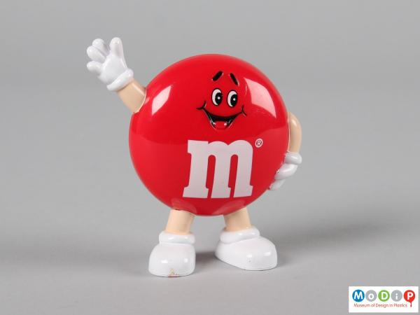 Front view of a brown M&M figure showing the smiling face and the limbs.