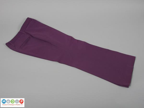 Side view of a pair of trousers showing them folded along the creaseline.