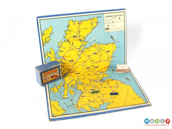 Front view of a Touring Scotland board game showing the board, box for the pieces and the metal cars.
