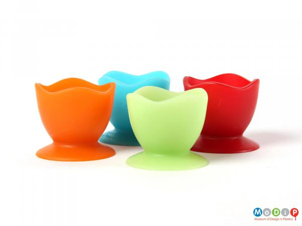 Side view of a set of Colin Ross egg cups showing the green and orange cups at the front with the blue and red cups behind.