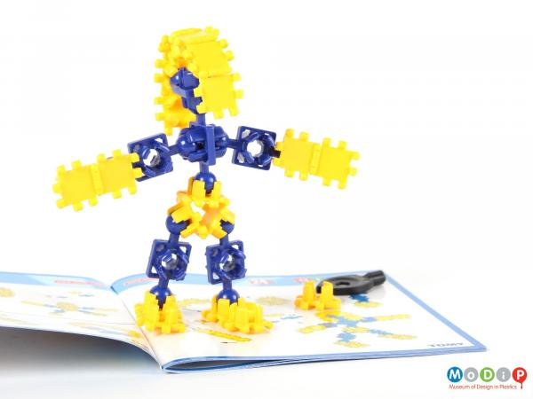 Side view of an Atollo construction set showing a figure made from the pieces.