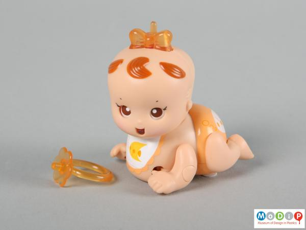 Side view of a Tomy Micro Babies showing the doll and her dummy which can be worn as a ring.