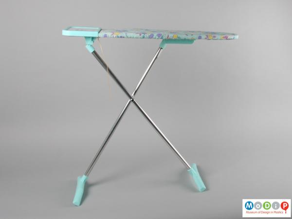 Side view of a toy ironing board showing the crossed legs.