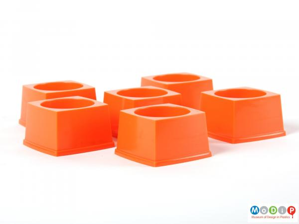 Side view of six stackable egg cups showing the sqaure shape and straight sides of the cups.