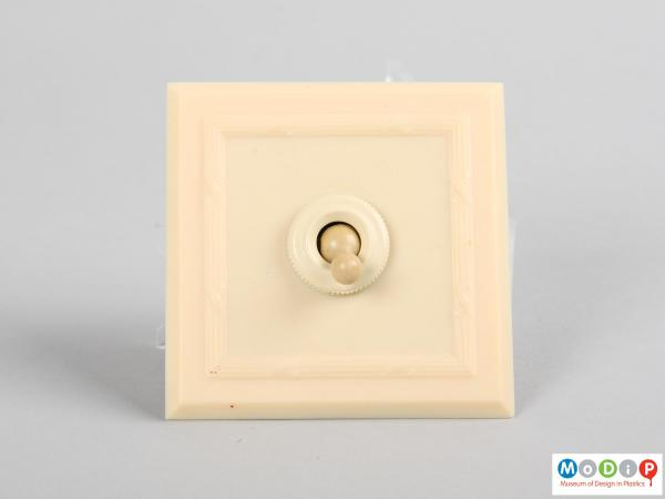 Front view of a light switch and surround showing the square bevelled edges.
