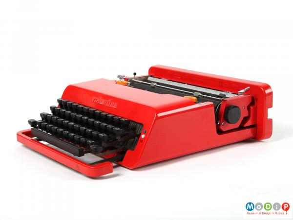 Side view of a Valentine typewriter showing the red body and black keys.