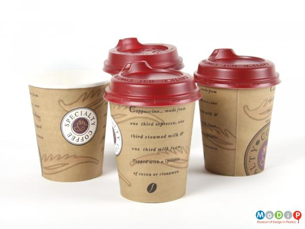 Side view  of three Smart Lids and paper cups showing the two different types of lid.