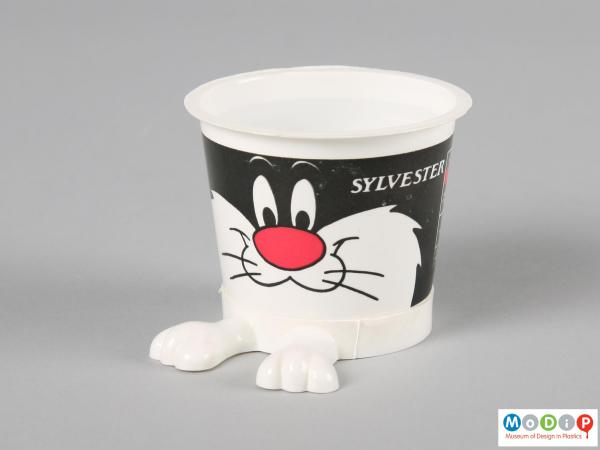 Side view of a Sylvester yoghurt pot showing the protruding legs at the bottom and printed face.