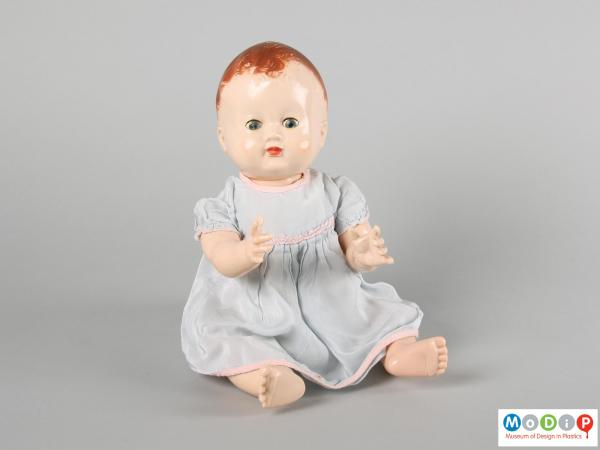 Front view of a Pedigree doll showing the doll in a seated position with arms foward and eyes open.