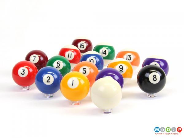 Side view of a set of pool balls showing the glossy surfaces.