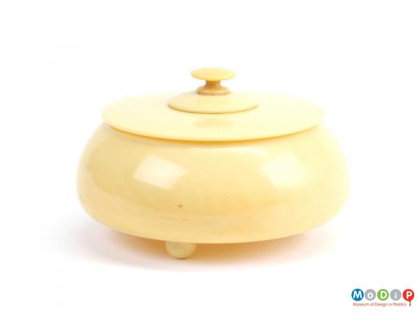 Side view of a powder bowl showing the flat lid and finial.