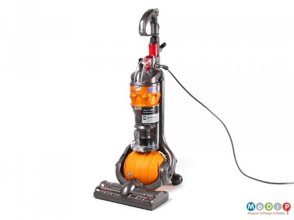 Side view of a Dyson DC24 All Floors vacuum cleaner showing the upright cleaner with its orange ball.