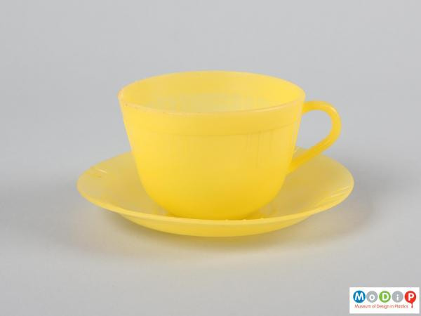 Side view of a cup and saucer showing the rounded handle.