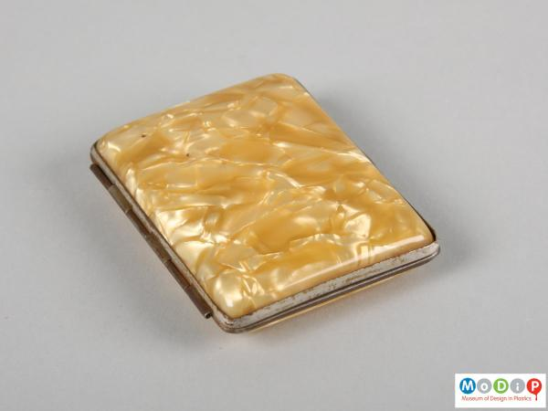 Side view of a cigarette case showing metal frame.