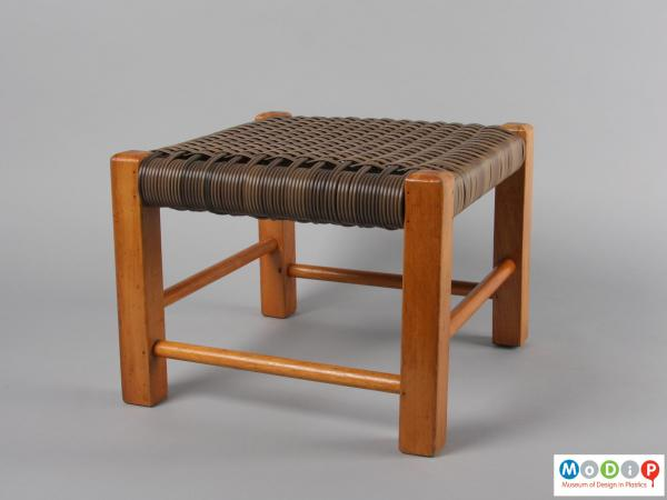 Side view of a footstool showing the wooden frame and woven seat.