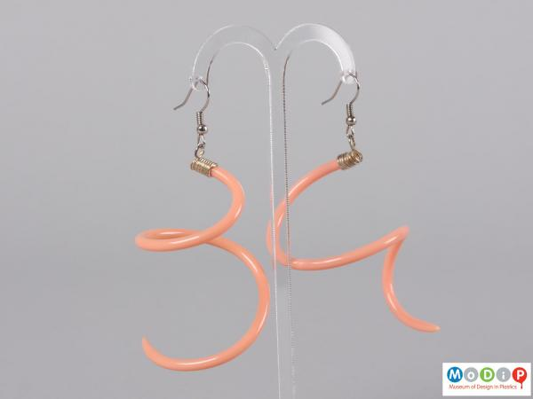 Side view of a pair of earrings made from knitting needles hanging on a stand.