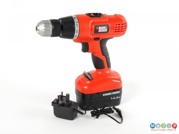 Side view of an electric drill showing the gun shaped drill with its electrical cable and plug.