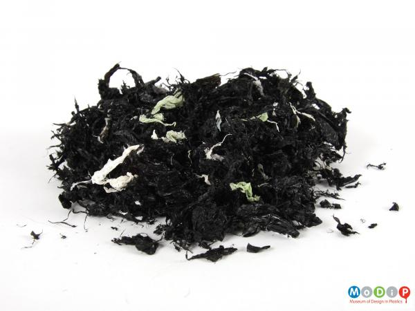 Side view of a pile of shredded flakes showing the mainly black pieces.