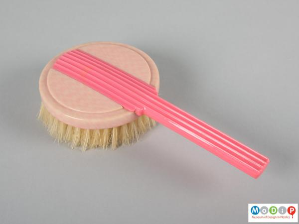 Top view of a brush showing the dark pink handle.