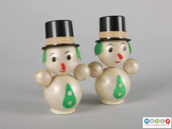 Front view of a pair of snowman showing their top hats and facial features.