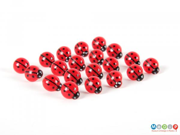 Top view of a set of drawing pins showing the red, black and white tops.