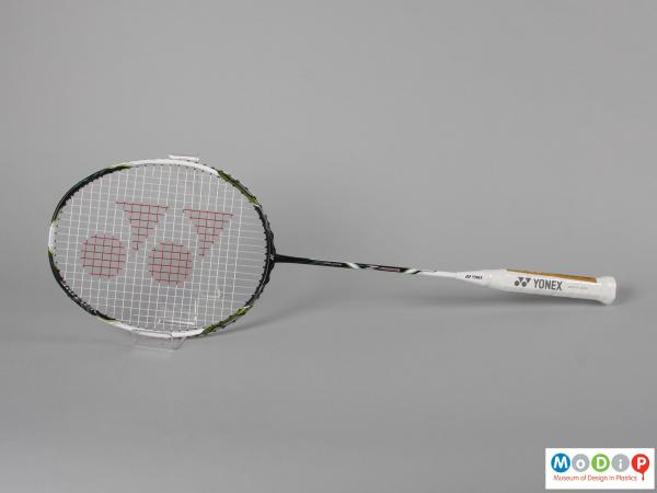 Side view of a badminton racket showing the egg shaped head and long, thin handle.