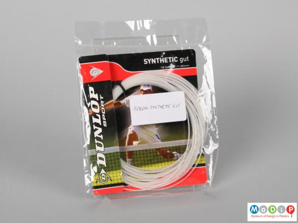 Front view of a length of tennis racket string showing the packaging.