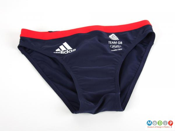 Front view of a pair of swimming trunks showing the red waist band and white printed logos.