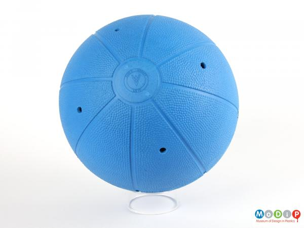 Side view of a goalbball showing the surface texture and the holes revealing the bell compartments.