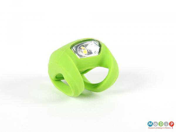 Front view of a bike light showing the white lens and green body.