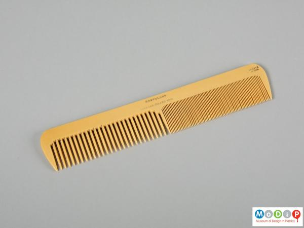 Side view of a comb showing the different sized teeth.