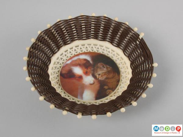 Top view of a basket showing the printed image of a puppy and kitten.