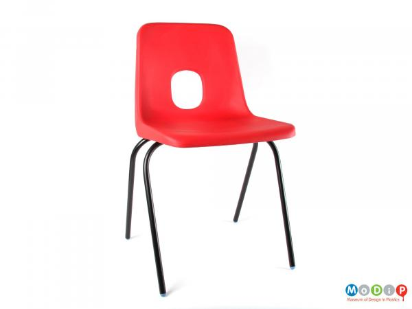 Front view of a chair showing the black legs and red seat.