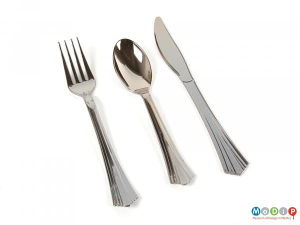 Top view showing a set of cutlery showing a fork, spoon, and knife.