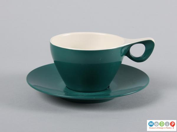 Side view of a cup and saucer showing the elegant handle.