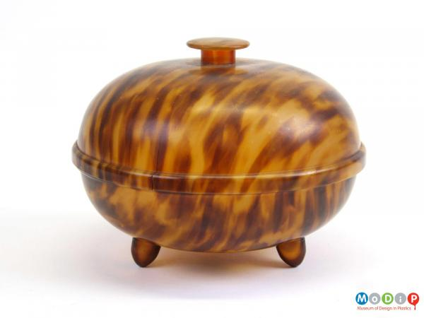Side view of a tortoiseshell effect powder bowl showing two feet