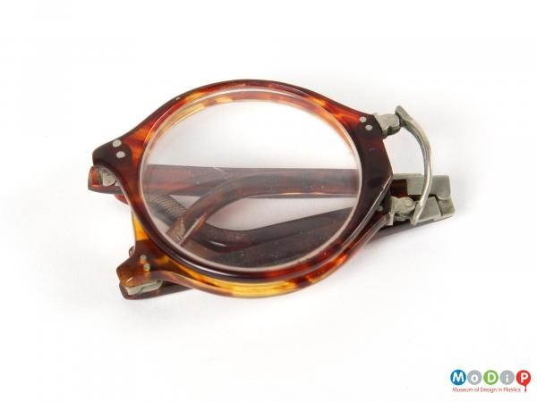 Front view of a pair of folding glasses showing the lenses and arms folded to their minimum size.