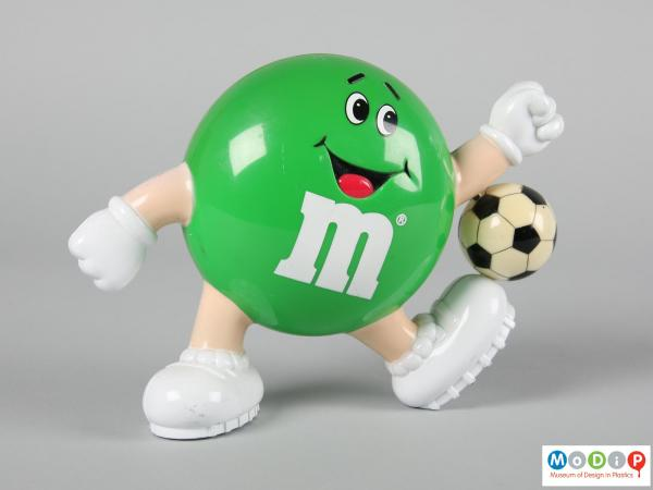 front view of a green M&M figure showing the smiling face and limbs.