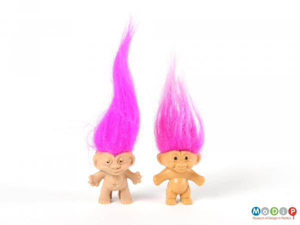 Front view of 2 trolls showing the long pink hair.