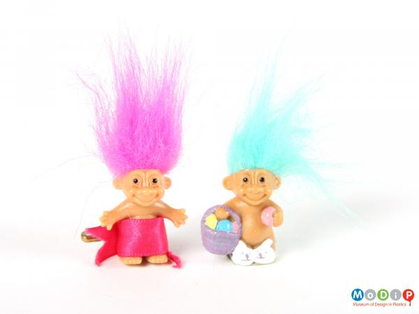 Front view of 2 trolls showing 1 with pink hair and the other with light blue hair.