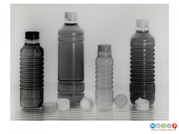 Scanned image showing four bottles and their related lids.
