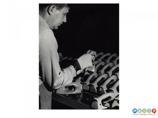 Scanned image showing a male worker tidying steam iron handles.