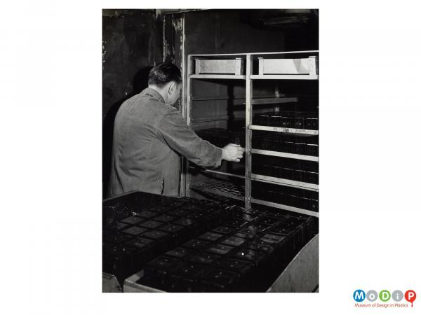 Scanned image showing a male worker moving trays of mouldings.