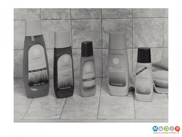 Scanned image showing 5 shmapoo and conditioner bottles in a bathroom setting.