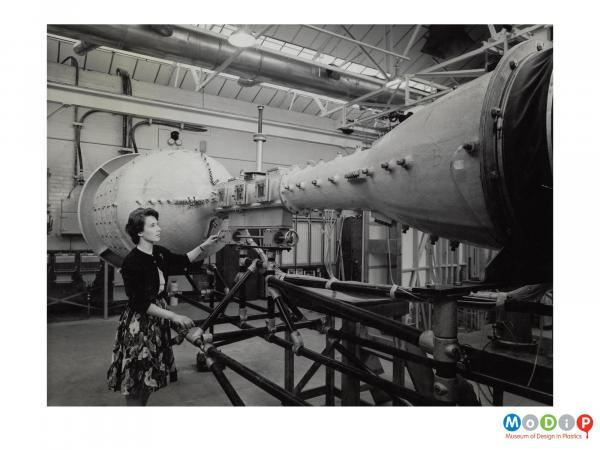Scanned image showing a woman looking at a wind tunnel.