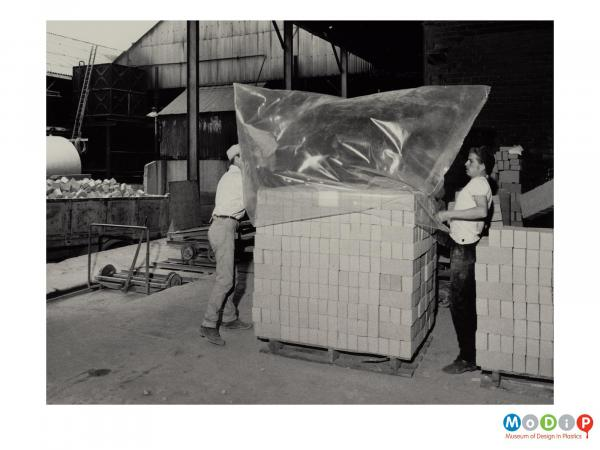 Scanned image showing 2 men covering a pallet load of bricks with a plastic bag.