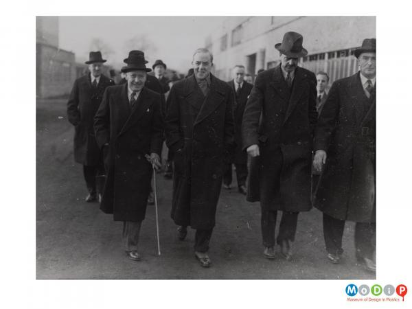 Scanned image showing a group of smartly dressed men.