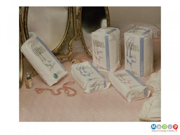 Scanned image showing 5 packets of sanitary products on a dressing table with a miror at the back.